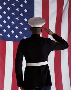 Man in U.s. Marine Corps Uniform Saluting American Flag --- Image by © Royalty-Free/Corbis